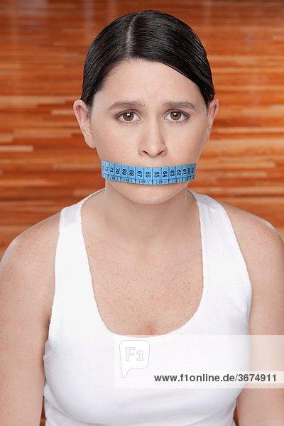 Frau über den Mund mit einem Maßband