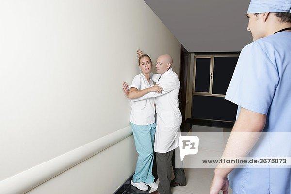 Männlichen Arzt flirtet mit weiblichen im Korridor krankenhaus krankenschwester