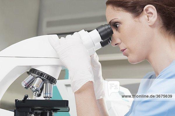 Weibliche Lab Technician analysieren eine Probe durch ein Mikroskop