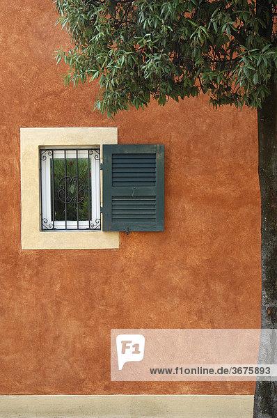 Vrgittertes Fenster in einer orangefarbenen Hauswand  Gardasee  Italien