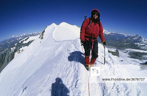 Bergsteigerin auf dem Gipfelgrat des Castor Wallis Italien