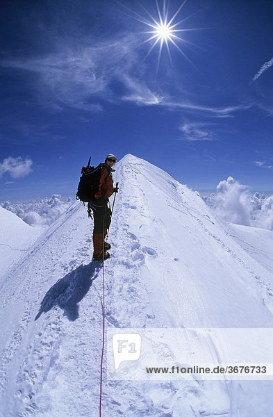 Bergsteigerin auf dem Gipfelgrat der Ludwigshöhe Wallis Schweiz