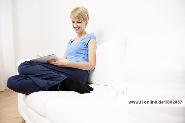 Young woman writing sketching on sofa