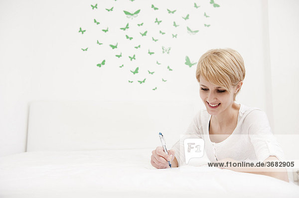 Young woman writing sketching on bed