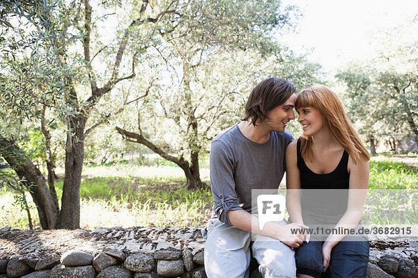Junges Paar auf der Wand sitzend