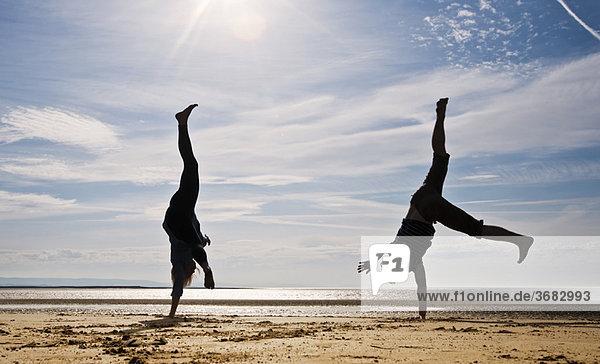 Zwei Personen  die am Strand fahren