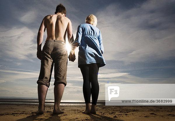 Paar hält sich am Strand an den Händen