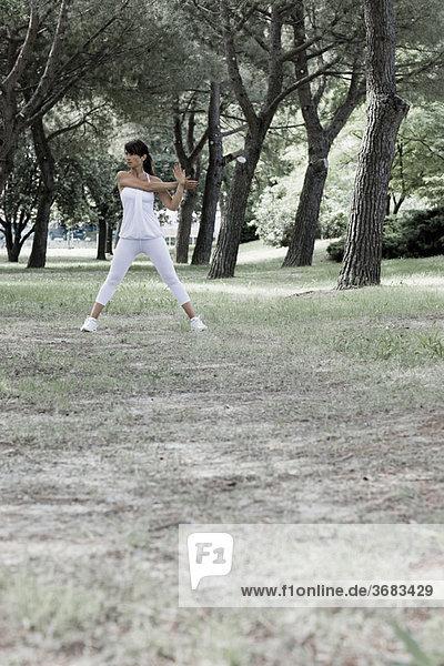 Frau  die sich in einem Park ausstreckt