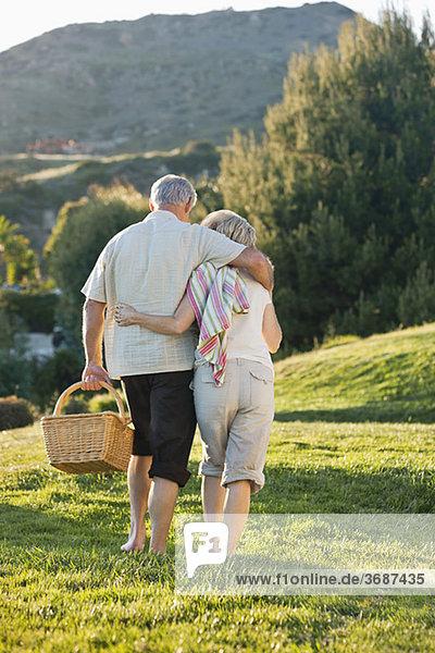 Seniorenpaar mit Picknickkorb auf einer Wiese