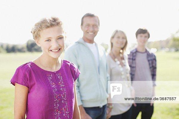 Lächelndes Mädchen mit Familie im Freien