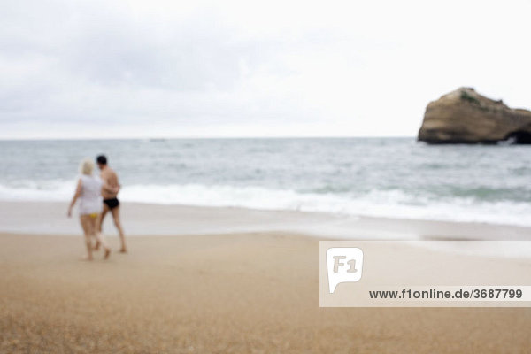 Ein Paar  das am Strand spazieren geht  defokussiert.