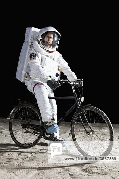Ein Astronaut auf einem Fahrrad auf dem Mond