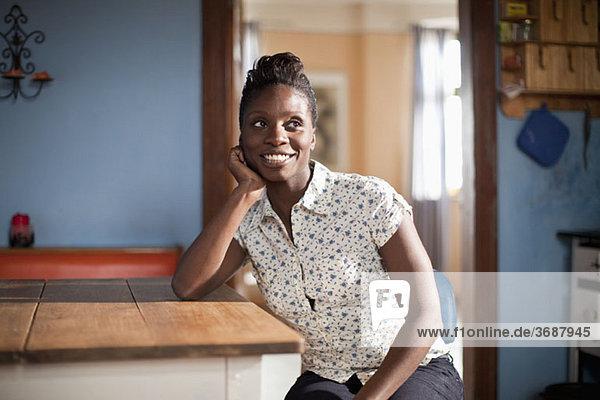 Eine junge Frau sitzt an einem Tisch in einer häuslichen Küche.