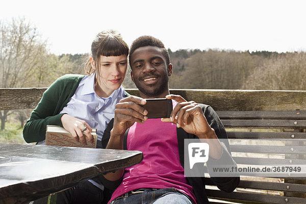 Ein Paar  das sich zusammen ein Smartphone ansieht.