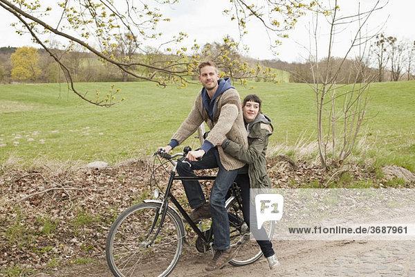 Ein Mann  der seine Freundin auf dem Land mit dem Fahrrad fährt.