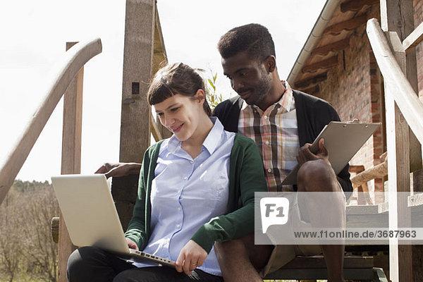 Ein Paar sitzt auf einer Treppe und schaut zusammen auf einen Laptop.