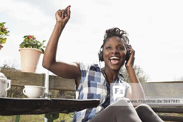 Eine Frau  die Kopfhörer hört  singt und tanzt.