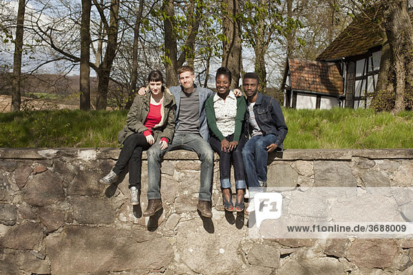 Four friends sitting on a stone wall