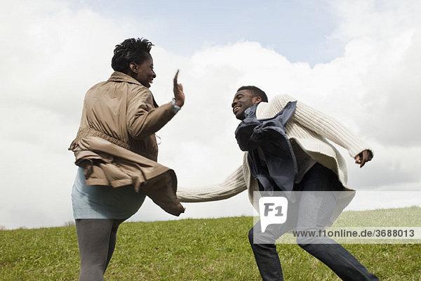 Ein junger Mann jagt seine Freundin einen Hügel hinunter.