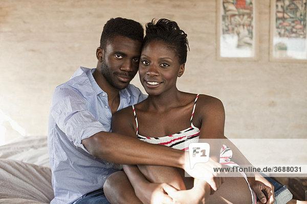 Ein junges Paar  das sich im Bett kuschelt.