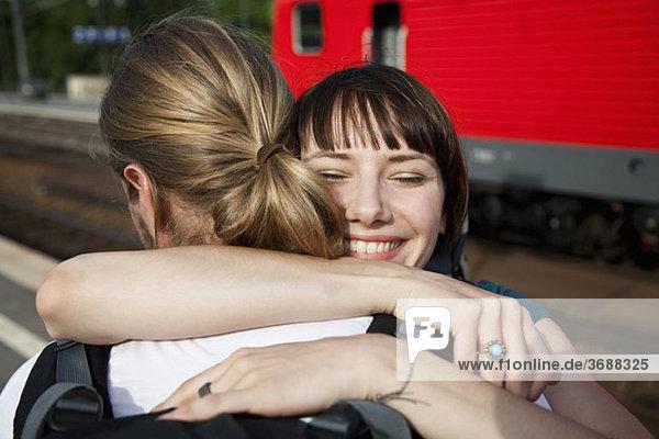 Eine glückliche Frau umarmt ihren Freund auf einem Bahnsteig.