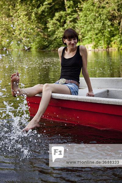 Eine junge Frau in einem Ruderboot  die mit dem Fuß ins Wasser spritzt.