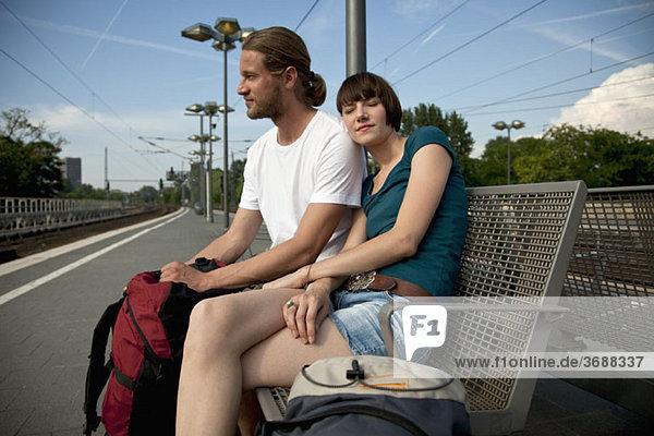 Ein gelangweiltes Backpacker-Paar  das auf einem Bahnsteig auf seinen Zug wartet.