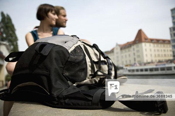 Ein Rucksack und ein junges Paar an der Spree  Berlin  Deutschland  Schwerpunkt Rucksack