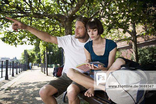 Ein junger Mann zeigt  während seine Freundin mit Unsicherheit auf eine Karte schaut.