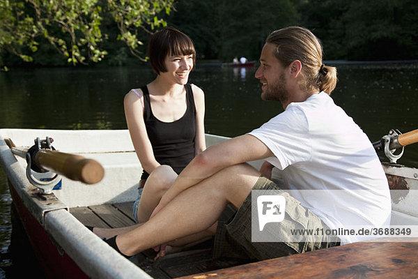 Ein junges Paar  das in einem Ruderboot redet.