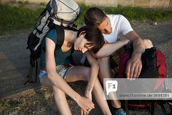 Ein Backpacker-Paar wartet am Straßenrand.