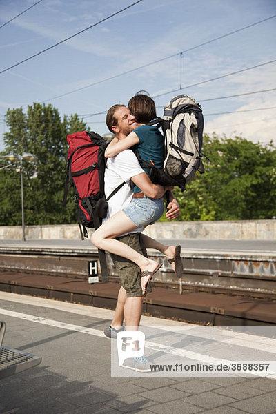 Eine ekstatische Frau umarmt ihren Freund auf einem Bahnsteig.