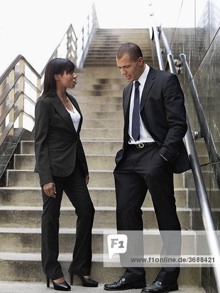 Ein Geschäftsmann und eine Geschäftsfrau  die vor einem Büro reden.