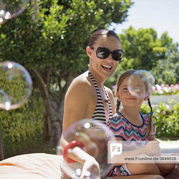 Seifenblasen  die von einer Mutter und einer Tochter  die zusammen im Freien sitzen  getragen werden.
