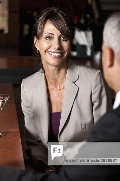 Eine Geschäftsfrau sitzt einem Kollegen an einer Bar gegenüber.