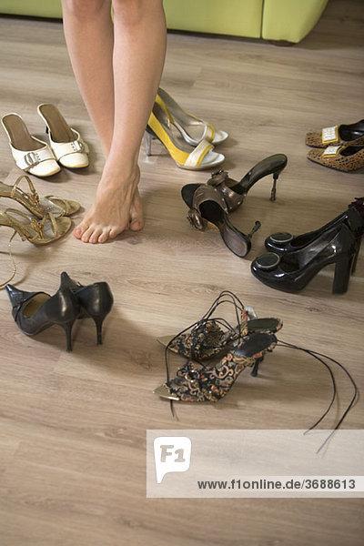 Eine Frau  die in der Mitte mehrerer Paar Schuhe steht.
