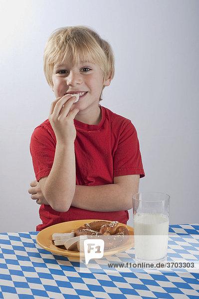 Junge  4-5 Jahre  isst Breze und Gelbwurst