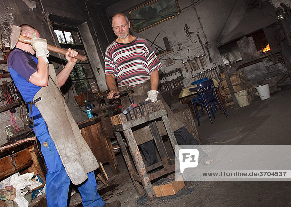 Blacksmiths working in a forge  Berlin  Germany