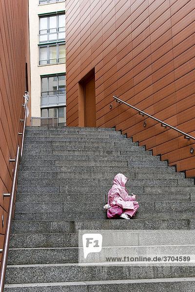 Kleinkind sitzt allein und verlassen auf den Treppenstufen zu einer Wohnanlage