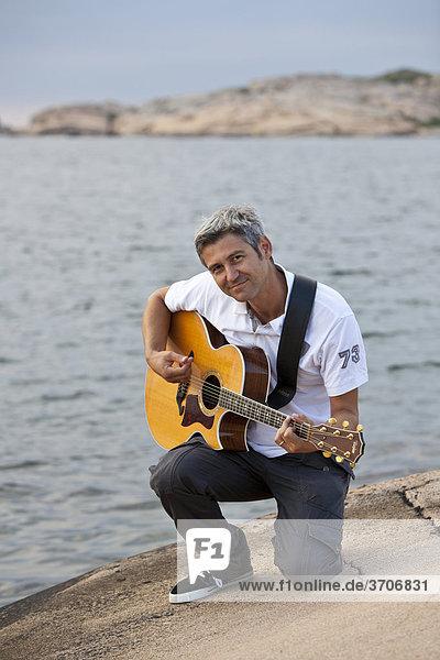 Mann spielt Gitarre an der Schärenküste in Sotenäs  Schweden