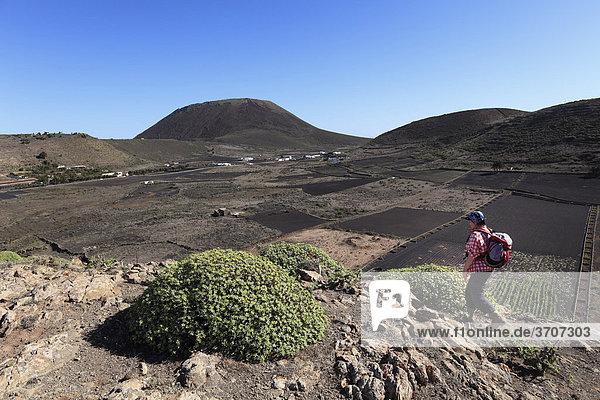 Frau mit Rucksack auf Risco de Famara  Valle de Guinate  hinten Vulkan Monte Corona  Lanzarote  Kanaren  Kanarische Inseln  Spanien  Europa