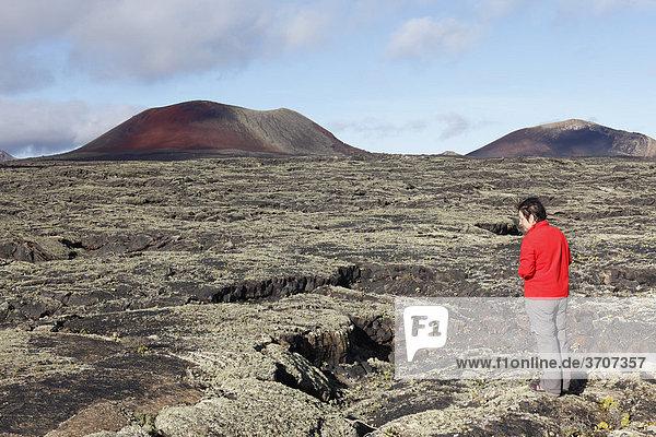 Vulkan Caldera Colorada und MontaÒa Ortiz  Frau im Lavafeld mit Flechten  Lanzarote  Kanaren  Kanarische Inseln  Spanien  Europa