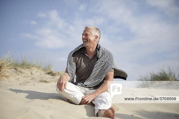 Männlicher Best Ager sitzt in den Dünen an der Nordsee in De Haan  Belgien  Europa