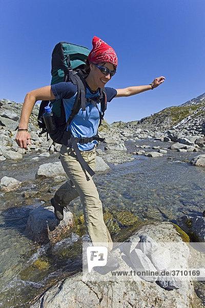 Junge Wanderin mit Rucksack springt über einen Bach  historischer Chilkoot Pfad  Chilkoot Pass  nahe dem See Crater Lake  alpine Tundra  Yukon Territory  British Columbia  B.C.  Kanada