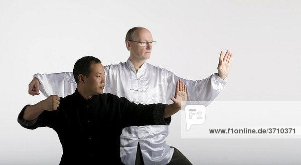 Deutsch-chinesische Freundschaft  zwei Taiji Meister in klassischer Taiji Bewegung  Chansi Gong  Westeuropa trifft Asien  in traditionellen Taiji-Jacken