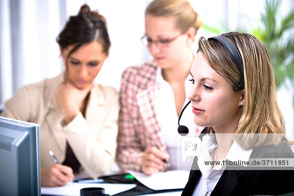 Junge Frau mit dem Headset im Büro