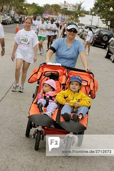 Florida  Miami Beach  ´Ocean Drive´  South Pointe 5K Run  benefit  runners  participant  walking  race  compete  Hispanic  woman  boy  girl  baby  toddler  mother  child  parent  sport  exercise  fitness  health  double stroller