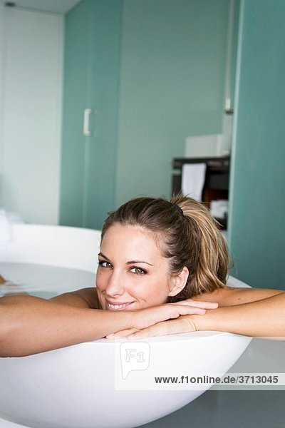 Blonde and beautiful woman enjoying a bath at home