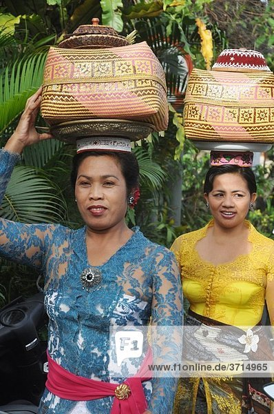Ubud (Bali  Indonesia): women in traditional dress  carrying a basket with offerings on their heads  going to a ceremony in a Hindu temple