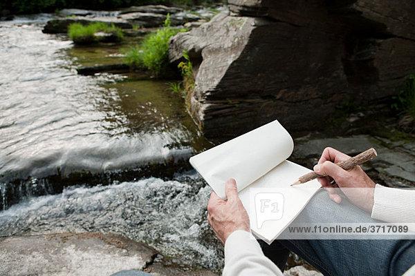 Senior man drawing outdoors  high angle
